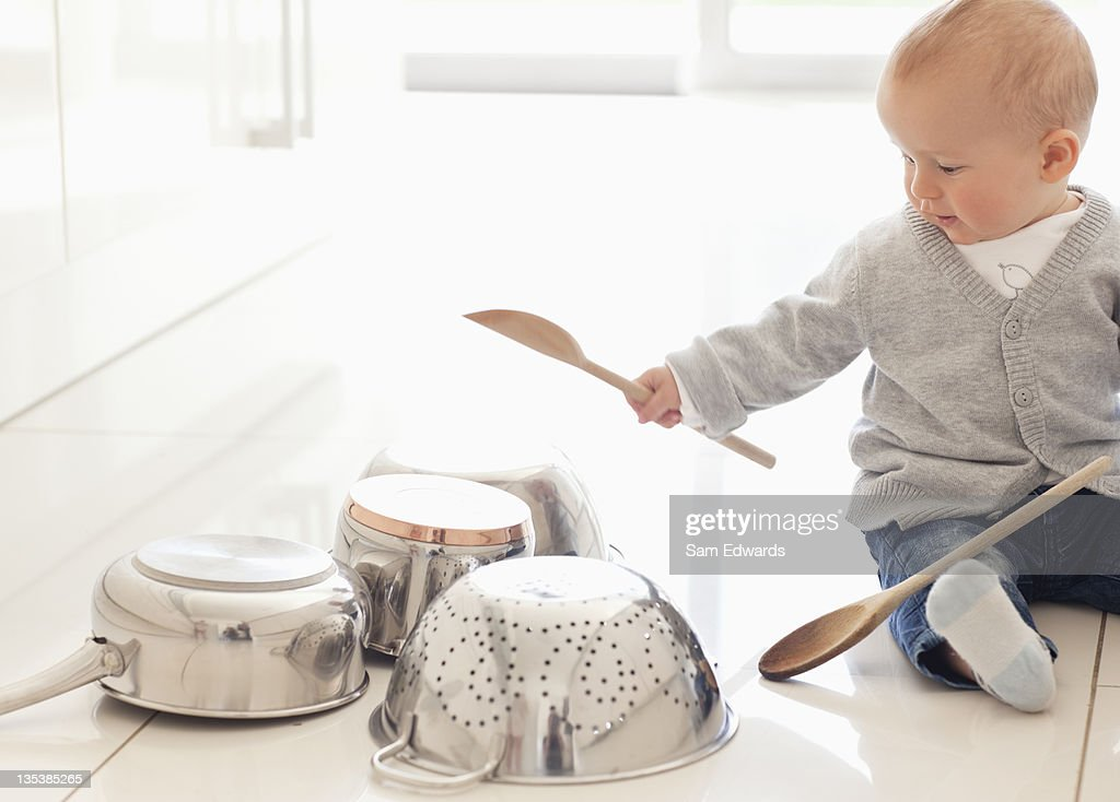 Baby banging on pots with wooden spoon : Stock Photo