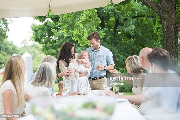 Baby being introduced to family on a garden party