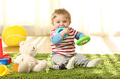 Front view portrait of a happy baby biting toys on a carpet at home