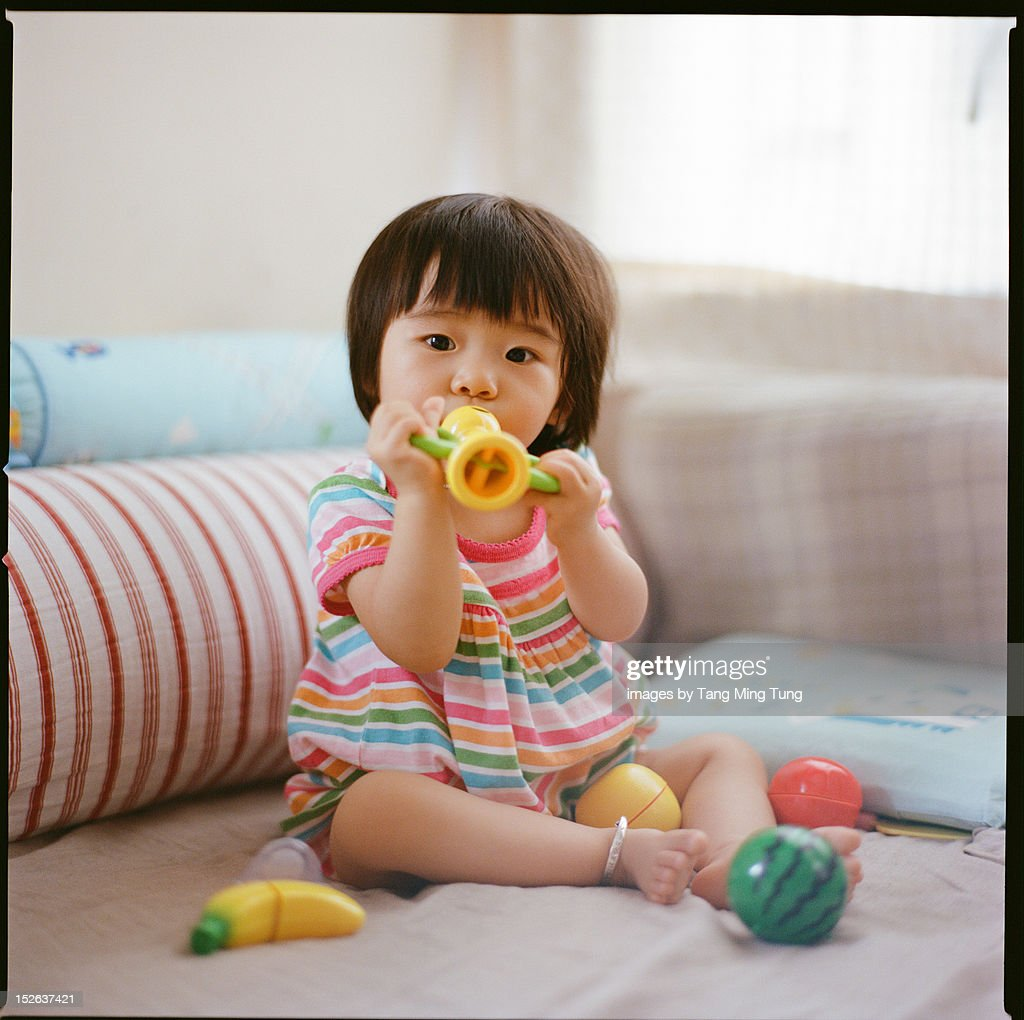 baby blowing a toy horn on the bed : Stock Photo