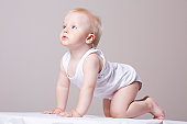 Baby boy (1-20 crawling, looking up, studio shot