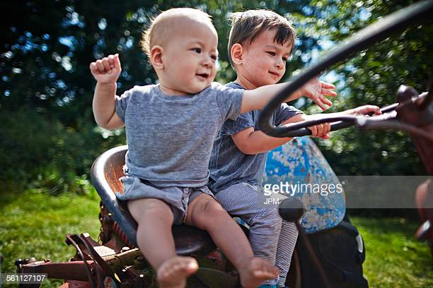 Baby boy and boy playing on old tractor
