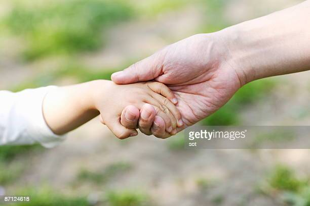 Baby boy and father holding hands,close up
