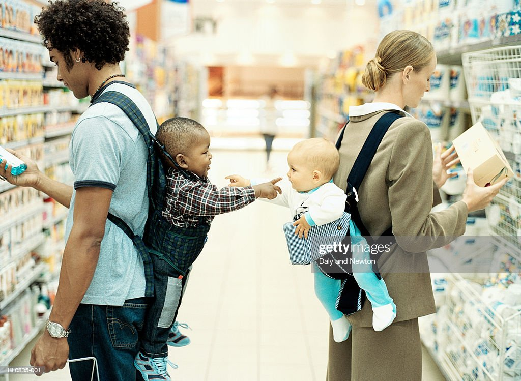 Baby boy and girl (9-15 months) in baby carriers, pointing, profile : Stock Photo
