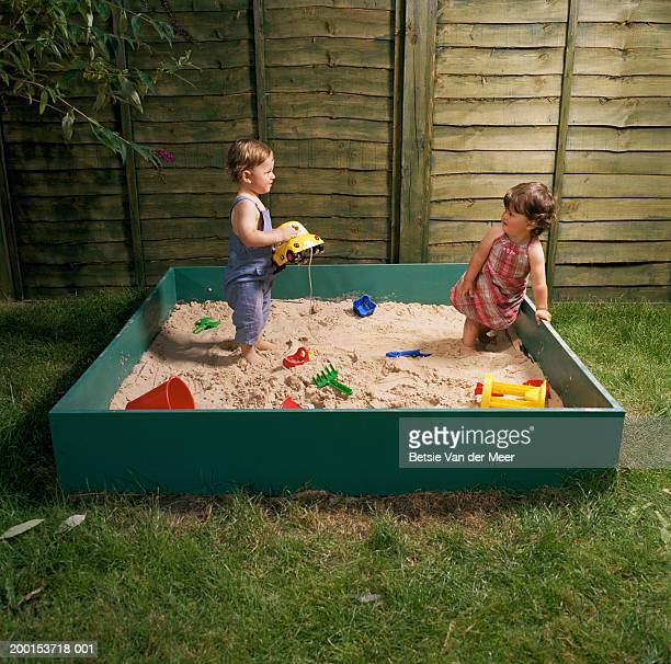 Baby boy and girl (12-15 months) standing in sand pit