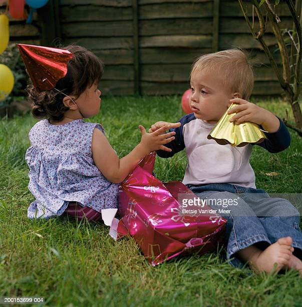 Baby boy and girl (12-15 month) touching hands, on grass by present