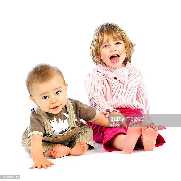 Baby boy and little girl smiling sitting on white
