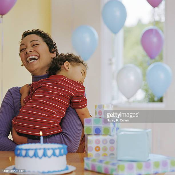 Baby boy (12-15 months) asleep in mother's arms at birthday party
