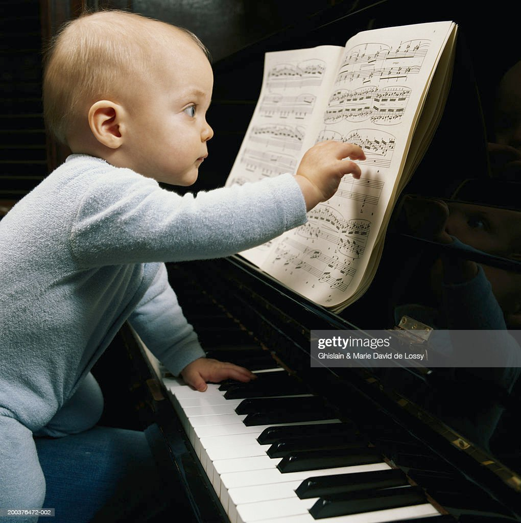 Baby boy (9-12 months) at piano touching score, side view : Stock Photo
