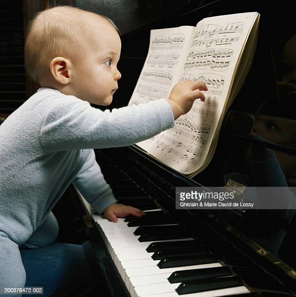 Baby boy (9-12 months) at piano touching score, side view
