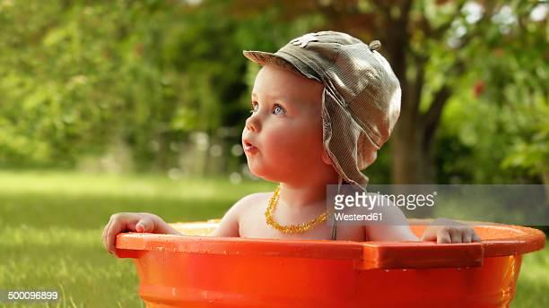 Baby boy bathing in orange tub in the garden