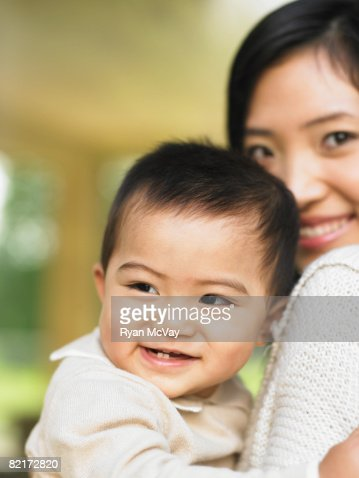 Baby boy being held by mother : Stock Photo