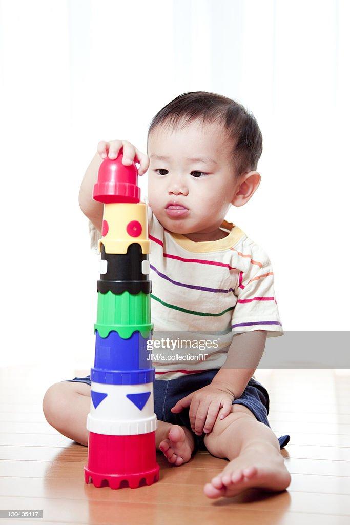 Building Toys For Babies : Baby boy building tower with toy blocks stock photo