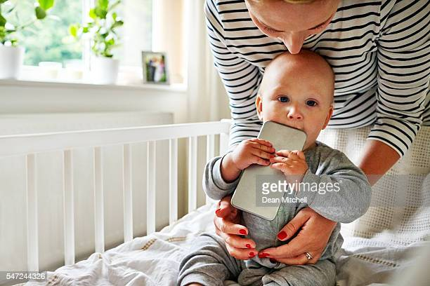 Baby boy chewing a cellphone in crib