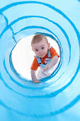 Baby boy (11-13 months) climbing into blue play tunnel