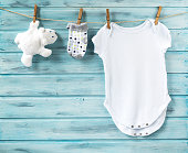 Baby boy clothes and white bear toy on a clothesline on blue wooden background