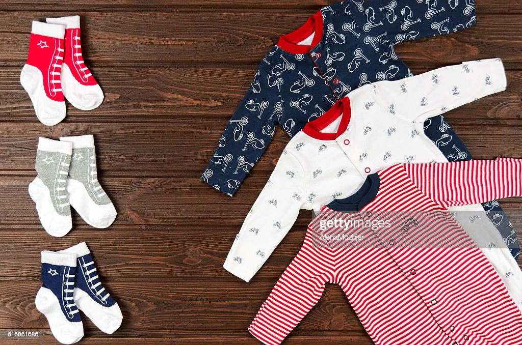 Baby boy clothes (sleepsuits and socks) on brown wooden backgrou : Stock Photo