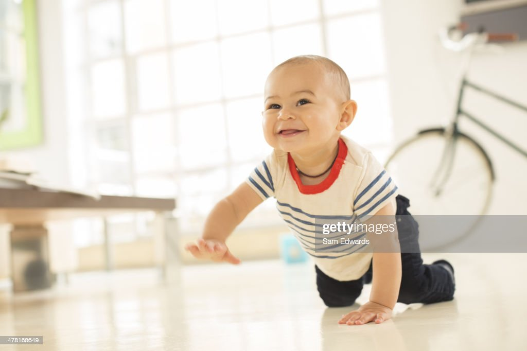 Baby boy crawling on living room floor : Stock Photo