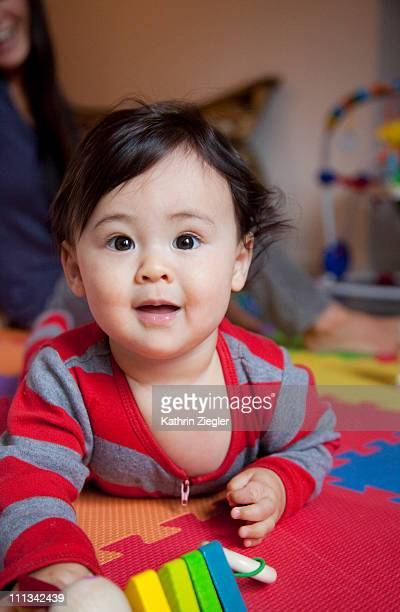 baby boy crawling on the floor, toy in his hand