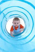 Baby boy (11-13 months) crawling through blue play tunnel