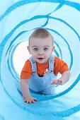 Baby boy (11-13 months) crawling through play tunnel