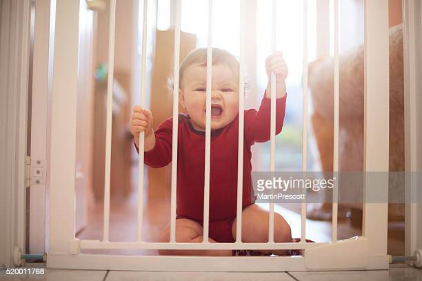 Baby boy crying at baby gate