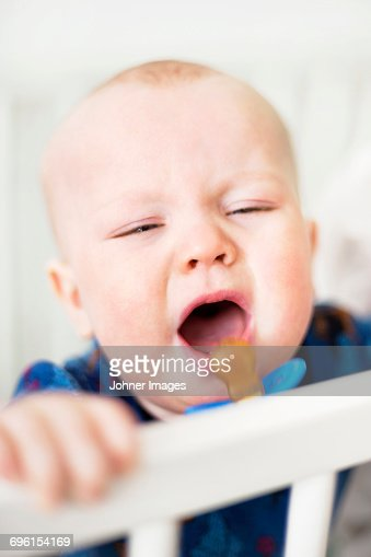 Baby boy crying in cot
