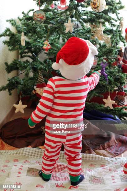 Baby boy decorating Christmas tree