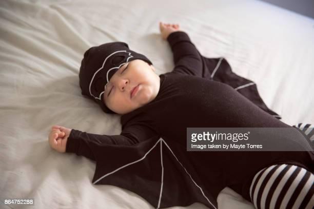 Baby boy dressed as a bat sleeping