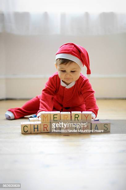 Baby boy dressed as Santa Claus with toy blocks reading Merry Christmas