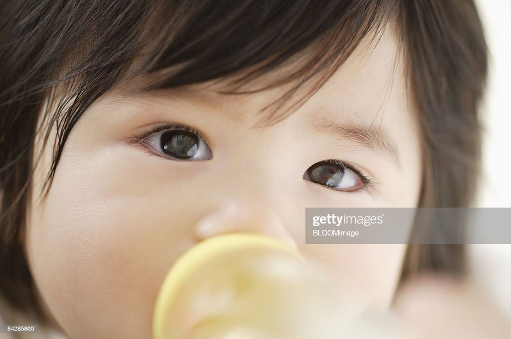 Baby boy drinking from baby bottle, close-up : Stock Photo