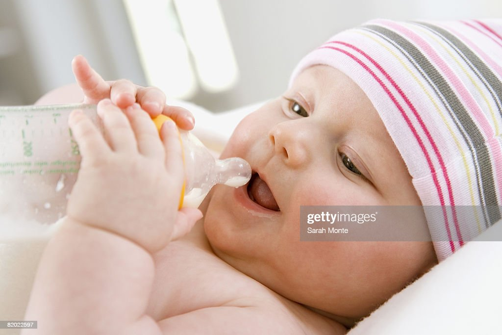 Baby boy (6-9 months) drinking milk from bottle, close-up