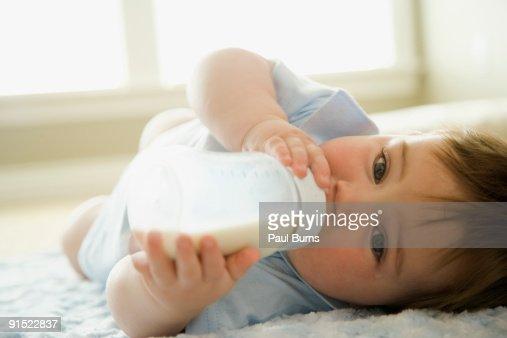Baby boy drinking milk from milk bottle : Foto de stock