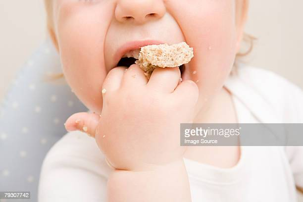 A baby boy eating a biscuit
