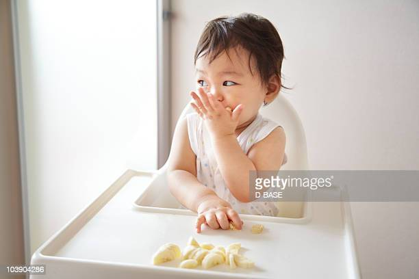 A baby boy eating  banana  in a high chair