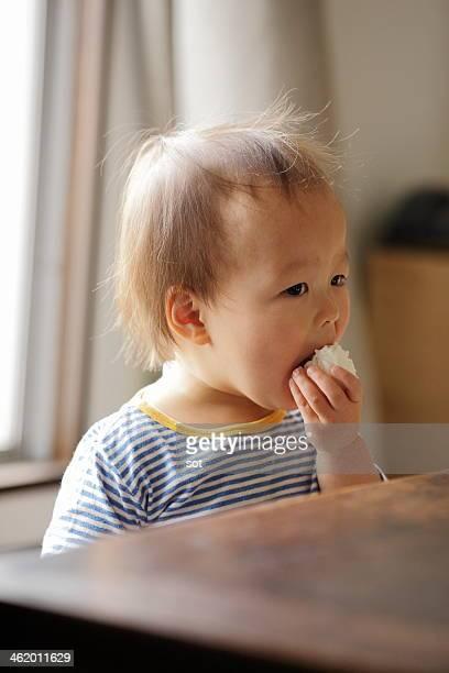 Baby boy eating rice ball at table