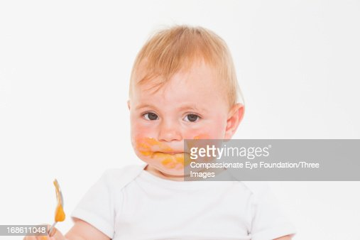 Baby boy eating with food all over face : Stock Photo