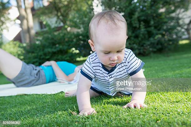 Baby boy exploring grass in lawn and his mother lying down in lawn, Munich, Bavaria, Germany