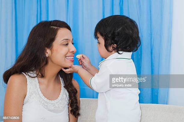 Baby boy feeding chips to his mother