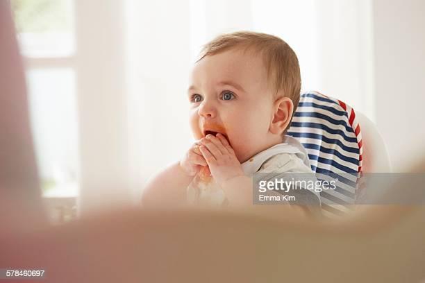 Baby boy feeding himself in baby chair