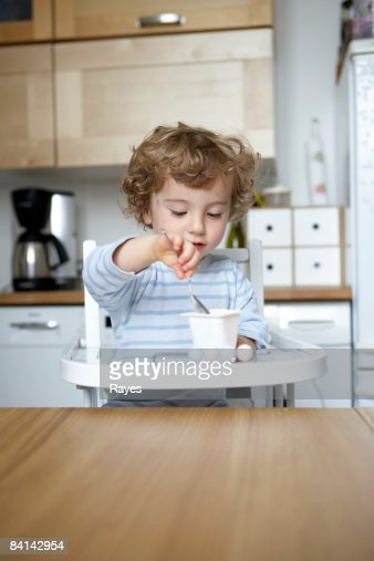 Baby boy feeding himself yoghurt : Stock Photo