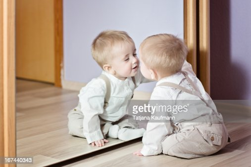 Baby Boy flirting with his Reflection : Stock Photo