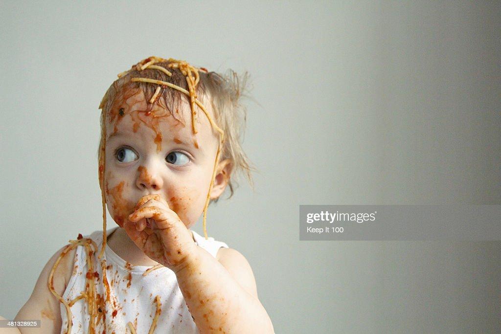 Baby boy getting messy eating spaghetti : Stock Photo