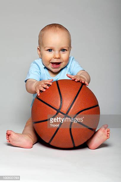 Baby boy (6-9 months) holding basketball, smiling