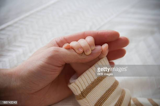 Baby boy holding mother's hand,  close up