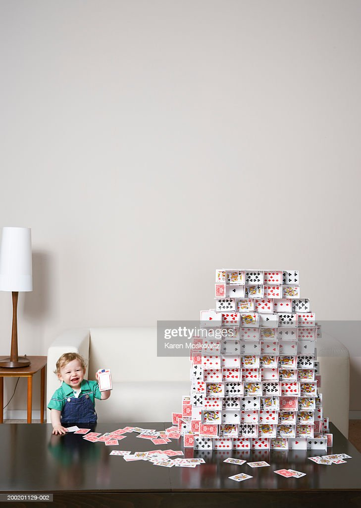 Baby boy (9-12 months) holding playing card box beside house of cards
