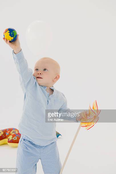 Baby boy holding up a ball