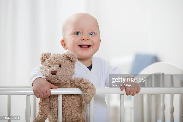 Baby boy in crib with teddy bear