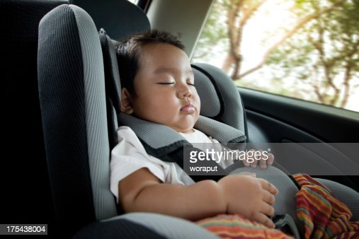 A baby boy in deep sleep in a car seat