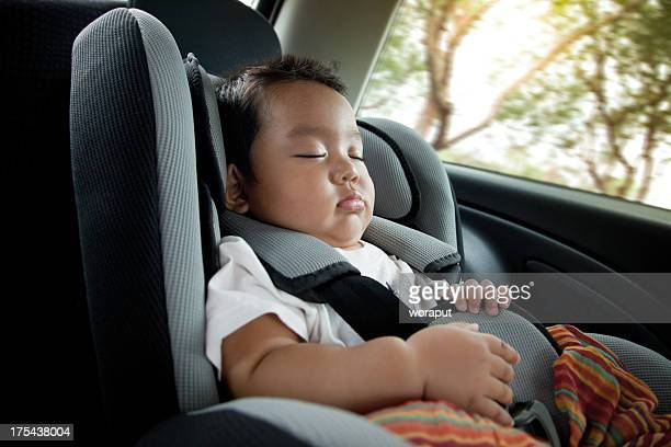 A baby boy in deep sleep in a car seat